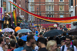 Portland Place, London, June 25th 2016. Thousands of LGBT people and their supporters gather for Pride in London, a colourful celebration of the hard-won rights of lesbian, gay, bisexual and transgender  people. PICTURED: A blast of glitter shoots over the thousands of people dancing in the streets of Soho.