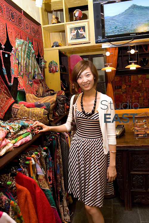 SHANGHAI, CHINA - September 15: Liu Yi browses clothes in 'Lumbini' shop, specialized in Tibetan clothes, in busy shopping neighborhood Taikang lu on September 15, 2009 in Shanghai, China. (Photo by Lucas Schifres/Getty Images)