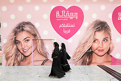 Women walk past billboard for new Victoria's Secret shop in City Centre shopping mall in Manama Kingdom of Bahrain