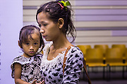 "17 JULY 2014 - BANGKOK, THAILAND: An undocumented Cambodian woman and her child wait for their ""mug shots"" for a temporary ID card at the temporary ""one stop service center"" in the Bangkok Youth Center in central Bangkok. Thai immigration officials have opened several temporary ""one stop service centers"" in Bangkok to register undocumented immigrants and issue them temporary ID cards and work permits. The temporary centers will be open until August 14.    PHOTO BY JACK KURTZ"