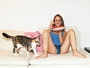 Young girl in hot pants eating watermelon on the sofa, open legs