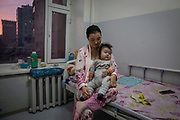 A mother holds her baby boy who has been suffering from pneumonia in a paediatric unit in one of the city hospitals in the capital  Ulaanbaatar, January 15, 2019. An ever-increasing number of children are suffering from respiratory related illnesses, stretching health infrastructures to the limit in Ulaanbaatar. Preliminary data suggests a 3.5-fold increase in fetal mortality rates between summer and winter, and a near-perfect correlation between stillbirths and air toxicity.