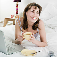woman lying on a white bed drinking coffee with a laptop computer