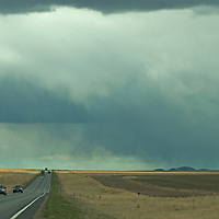 Cars & semi trucks speed past empty ranchlands on U.S. Highway 287, north of Three Forks, Montana.