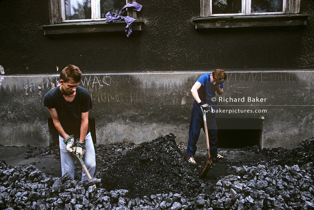 Young men shovel brown coal from street level, and into a cellar after being dumped by delivery men on a street in Aue, a mining town in the Ore Mountains known for its copper, titanium, and kaolinite. The town was a machine-building and cutlery manufacturing centre in the East German era with a population of roughly 18,000 inhabitants. It was the administrative seat of the former district of Aue-Schwarzenberg in Saxony and part of the Erzgebirgskreis since August 2008, on 15th June 1990, in Aue, Saxony, Germany.
