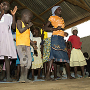 Sudanese children dance at a prayer meeting. This minority Christian community was relocated to a transit camp by the UNHCR after its church was burned down in an arson attack. Dadaab Refugee Camp, North Eastern Kenya.