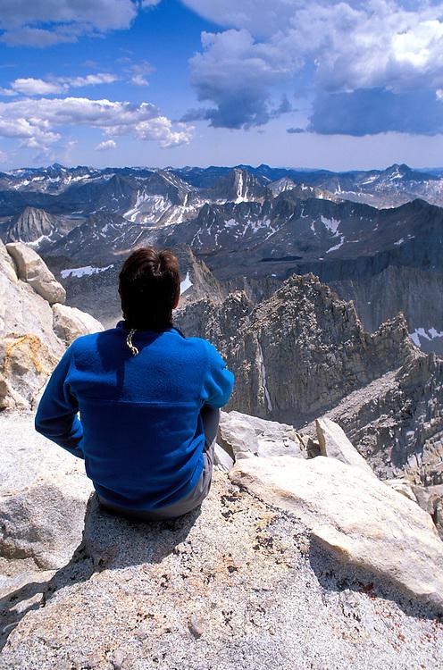 Climber looking out from the summit of Bear Creek Spire, John Muir Wilderness, Sierra Nevada Mountains, California USA