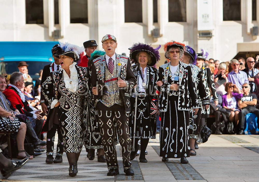 Pearly Kings and Queens Harvest Festival celebrations at Guildhall Yard. The annual event features early English entertainment including maypole dancing, Morris dancers and a marching band. The Chelsea pensioners & all the mayors of London take part in this traditional London event.<br /> The London tradition of the Pearly Kings and Queens began in 1875, by Henry Croft. Inspired by the local Costermongers, a close-knit group of market traders who looked after one another and were recognisable by buttons sewed onto their garments, Henry went out on the streets to collect money for charity, wearing a suit covered in pearl buttons to attract attention. When demand for his help became too much, Henry asked the Costermongers for assistance, many of whom became the first Pearly Families. Today, around 30 Pearly Families continue the tradition to raise money for various charities.