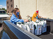 """11 MAY 2020 - DES MOINES, IOWA: GRACE OSTRANDER places food packages into the bed of a client's pickup truck at a """"no touch"""" emergency food pantry at DSM First Church in Des Moines. The emergency pantry at DSM First Church expanded from distribution one day a week to three days per week after the COVID-19 pandemic forced the closure of many Iowa businesses. Food banks and emergency pantries in Iowa continue to see increased demand for services, even though the governor is reopening the state's economy. Iowa's unemployment rate for April hasn't been released yet, but based on national trends, it is expected to soar to well over 10% from 3.8& in March. COVID-19 infections continue to skyrocket. On Monday, 11 May, the governor announced that 12,373 people tested positive for coronavirus (SAR-CoV-2) and  271 had died.            PHOTO BY JACK KURTZ"""