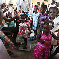 Children gather around a scale during a 'Celebration of Life' ceremony in Welsh, Haiti.