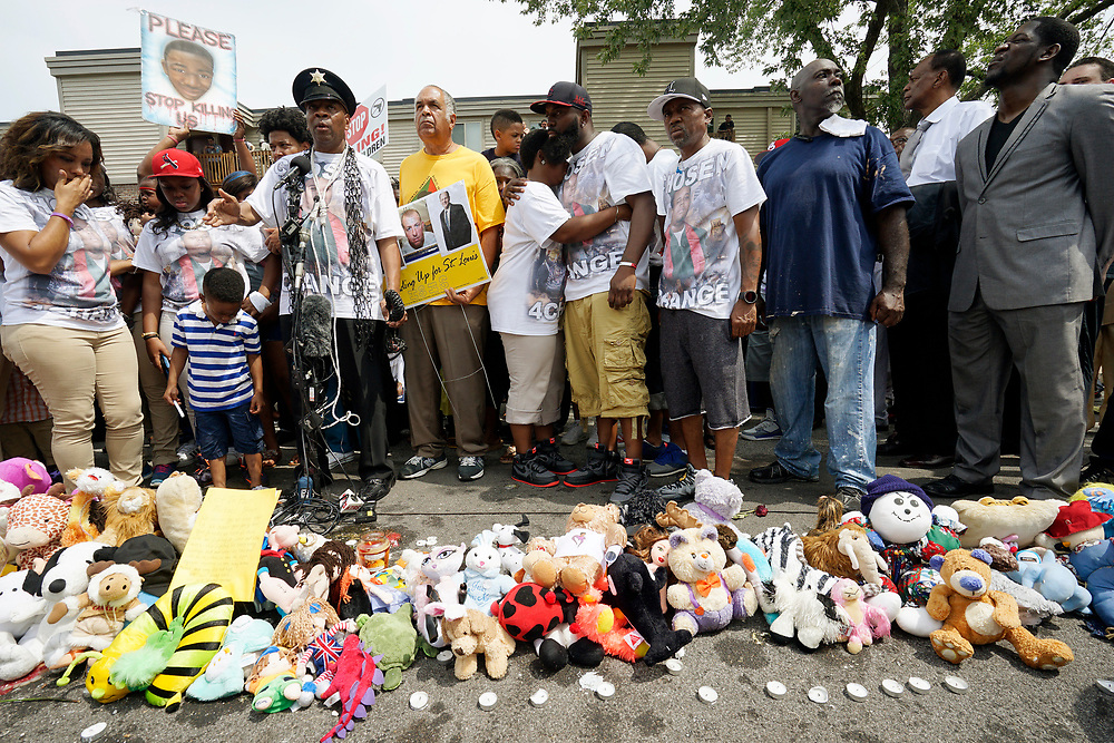 Michael Brown Sr., (C) at the spot where his son was killed, hugs his wife Cal Brown at an event to mark the one year anniversary of the killing of son Michael Brown Jr. in Ferguson, Missouri August 9, 2015.  Several hundred people gathered in Ferguson, Missouri, on Sunday to mark the one-year anniversary of the shooting death of an unarmed black teenager by a white police officer that sparked protests and a national debate on race and justice.  REUTERS/Rick Wilking
