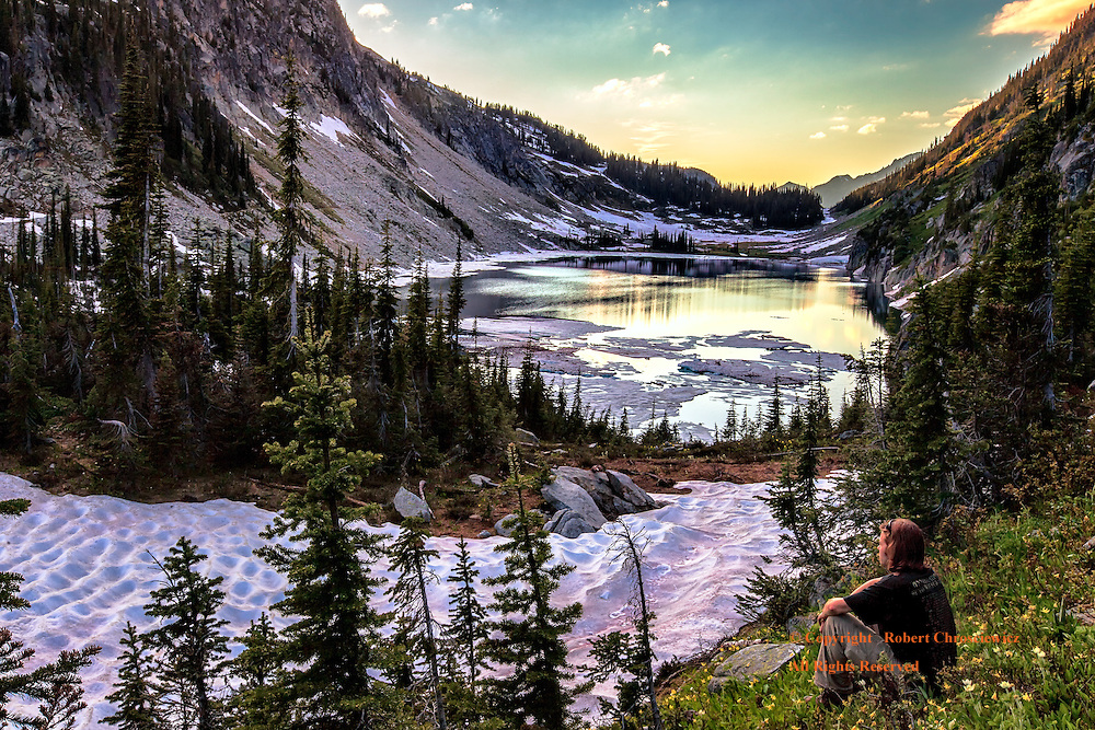 Rugged Kokanee Lake: A young man takes in the spectacular rugged landscape of Lake Kokanee at sunset, Kokanee Provincial Park, Nelson British Columbia Canada.