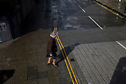 Seen from a London bus, an aerial view of an elderly woman who is about to cross a quiet side street.