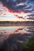 The rising sun colors the clouds and their reflection in lake bright red with dark blue shadows, Purezers Lake nature trail, Latvia Ⓒ Davis Ulands   davisulands.com