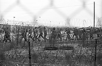Soldiers seen within the Greenham Common Airbase during the period of the women protests in 1982. The military patrol the perimeter fences for security during the cruise missile demonstrations. Photograph by Jayne Fincher