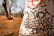 A girl sits under a tree at a the Yida refugee camp registration center. Every day 200-700 new refugees arrive from the Nuba mountains, many of them are unaccompanied minors . The Lost boys of Sudan may be the best known example of the horror of Sudan's civil war, a conflict that was supposed to end with the independence of the South last July.  Countless South Sudanese boys were forced to flee, separated from their families, walking for days and weeks across hostile lands to the relative safety of a refugee camp. Many died on the way. .Now, this story is repeating itself as thousands of children, separated from their families by constant bombardment, starvation and battles are fleeing the same unresolved conflict, this time in the Nuba mountains of Sudan, where the Khartoum government has been at war with it's own people for over a year. The Sudan government's endless bombing campaigns of civilian targets like schools, churches, markets and boreholes has divided up families and separated children from their parents, and orphaned others..Over 3000 of these children have ended up at the Yida refugee camp, a controversial refuges for the Nuban people close to the North South border that the UN refuses to recognize as a camp for fear of being seen as supporting the rebels. The children have horrific stories. 20 year old John first lost his family in a bombing, he then lost his two younger brothers to starvation, without even the energy to bury them, he walked south for days until he arrived in Yida. 12 year old Rose fled with her entire boarding school after it was bombed and many of here fellow students and teachers killed. Robert watched his family stoned to death after a desperate group of refugees was ambushed by a Northern militia on the border..A few volunteer caretakers and teachers tend to the children. 22 year old Jamina who was separated from her own mother for 11 years during the last war. Today she watches over 500 girls in the same position. Packed into gr