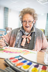 Senior woman painting fruit using water color