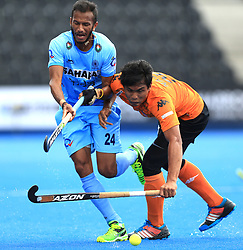 India's Sunil Sowmarpet and Malaysia's Najmi Jazlan battle for the ball during the Men's World Hockey League match at Lee Valley Hockey Centre, London.