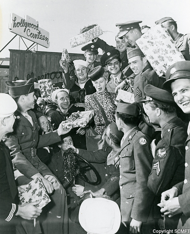 1943 Irene Manning hands out Christmas gifts at the Hollywood Canteen.