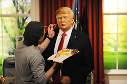 Chris Garigulo applies make up to a wax figure of Donald Trump in the Oval office, as it is unveiled at Madame Tussauds in London, ahead of his inauguration as the 45th US president.