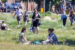Licensed to London News Pictures. 14/06/2021. London, UK. Scorcher. Sunbathers and picnickers enjoy the sunshine on Wimbledon Common southwest London today. Weather experts have forecast very warm weather for the next few days for the South East and London with temperatures predicted to hit up to 30c. Photo credit: Alex Lentati/LNP