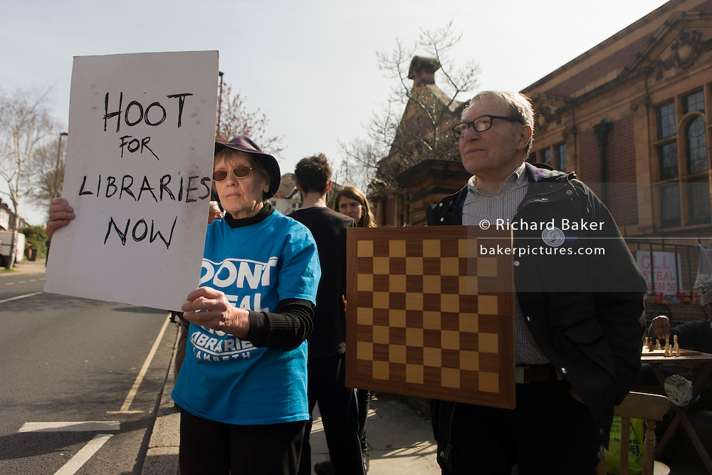 London, UK 2nd April: A campaigner asks motorists to hoot their horns as they pass Carnegie Library, in Herne Hill, south London on 2nd April 2016. The angry local community in the south London borough have occupied their important resource for learning and social hub for the weekend. After a long campaign by locals, Lambeth have gone ahead and closed the library's doors for the last time because they say, cuts to their budget mean millions must be saved. A gym will replace the working library and while some of the 20,000 books on shelves will remain, no librarians will be present to administer it. London borough's budget cuts mean four of its 10 libraries will either close, move or be run by volunteers. ©Richard Baker / Alamy Live News.