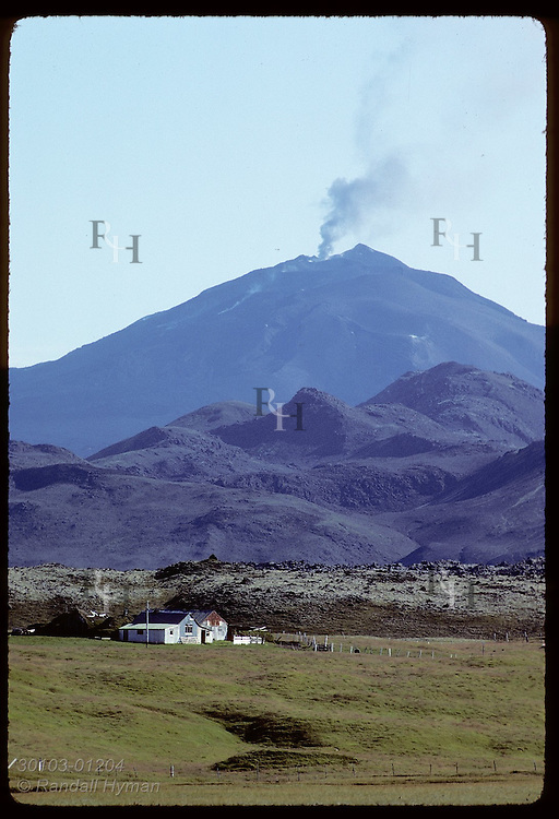Kot farmhouse is dwarfed by Mount Hekla, still smoking the day after August 1980 eruption. (v) Iceland