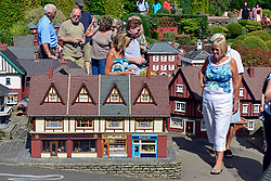 © Licensed to London News Pictures. 29/08/2013. Beaconsfield, UK A woman dwarfs a model house. People enjoy the sunshine and hot weather at Bekonscot Model Village in Berkshire today 29th August 2013. Bekonscot Model Village and Railway is the world's oldest and original model village, opening for the first time in 1929. With over 80 years of history, huge model railway, 1.5 acres of well kept gardens and finely detailed model buildings. Photo credit : Stephen Simpson/LNP