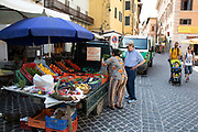 Fruit and vegetable stall seller in the Market Square in Spoleto, Umbria, Italy. Piazza del Mercato, located in the historical centre of Spoleto.