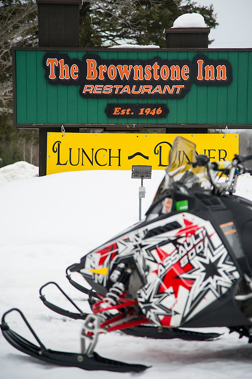 Snowmobiles parked outside The Brownstone Inn of AuTrain Michigan.
