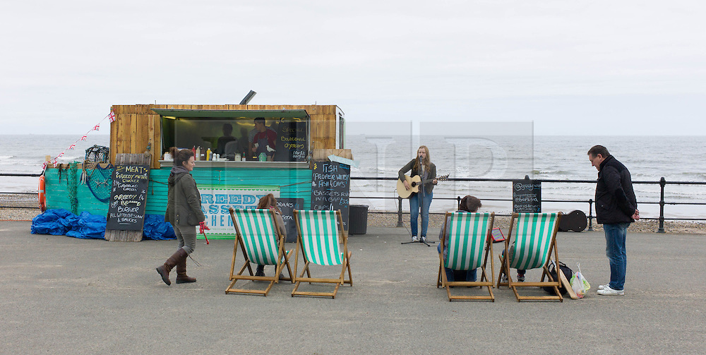 © Licensed to London News Pictures. 01/06/2013<br /> <br /> Saltburn, Cleveland, United Kingdom<br /> <br /> Entertainment is provided next to a food stall on the lower promenade in Saltburn on the first day of summer.<br /> <br /> Photo credit : Ian Forsyth/LNP