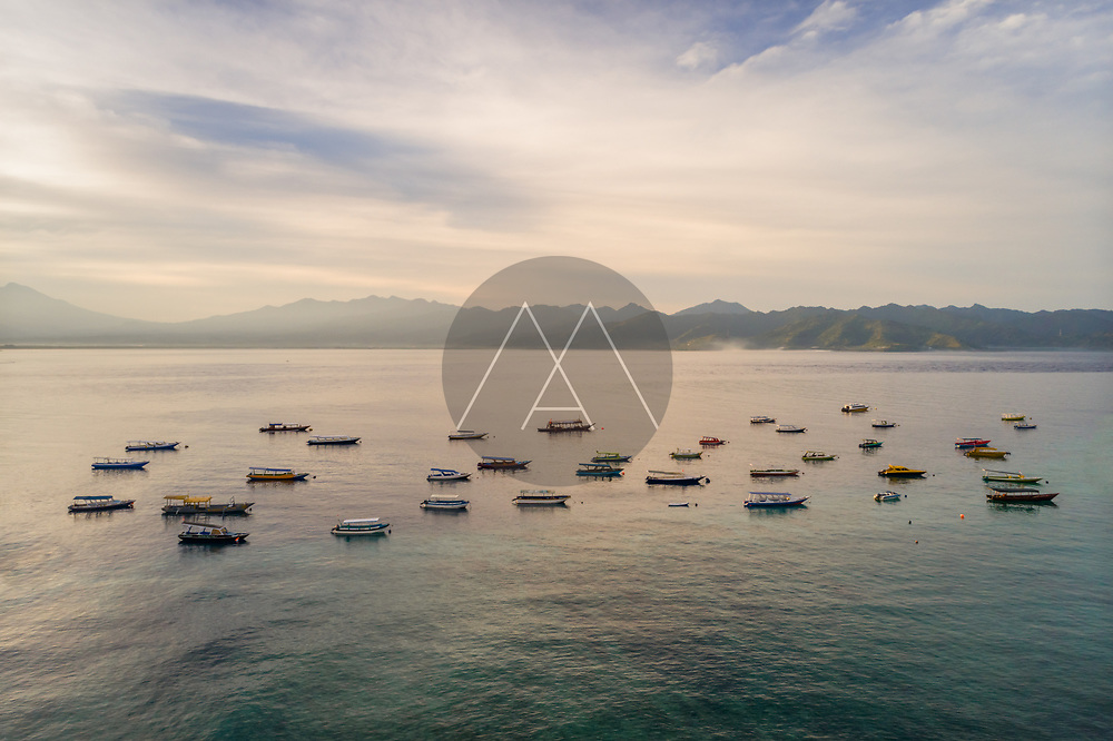 Aerial view at group of boats anchored next Gili Trawangan island during sunset.