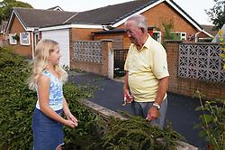 Elderly neighbour talking to girl over garden wall,