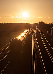 © Licensed to London News Pictures. 19/01/2014. Worting Junction, Worting Village, Hampshire, UK. A South West Trains service from London Waterloo approaching Worting Junction in Hampshire as the sun sets. Photo credit : Rob Arnold/LNP