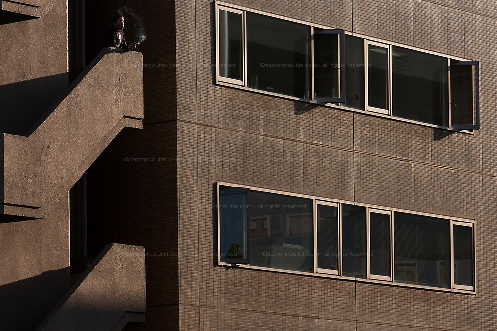 A Japanese salaryman or male office worker smokes on the outside stairs of an office building near Iidabashi, Tokyo, Japan. Friday May 17th 2013
