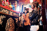 Young woman praying in front of an altar in Quan Thanh pagoda during Tet in Hanoi, Vietnam