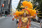 A marcher wears an ornate yellow and orange costume with bright feathers and sunbursts.