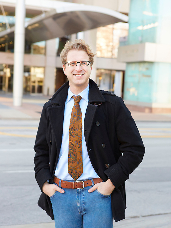 Portrait photograph of smiling lawyer standing in front of law firm