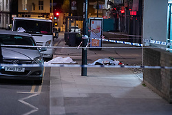 © Licensed to London News Pictures. 10/04/2021. London, UK. A sheet covers the body of a 17-year-old boy who was fatally stabbed in Sydenham. Police were called to Hazel Grove, junction with Sydenham Road, at 19:19BST on Saturday, 10 April after reports of a male lying injured on the ground. Officers attended with medics from the London Ambulance Service and the London Air Ambulance. They found a 17-year-old male who had been stabbed. Despite the best efforts of the emergency services, he was pronounced dead shortly after 20:00hrs. His next of kin have been informed. Photo credit: Peter Manning/LNP