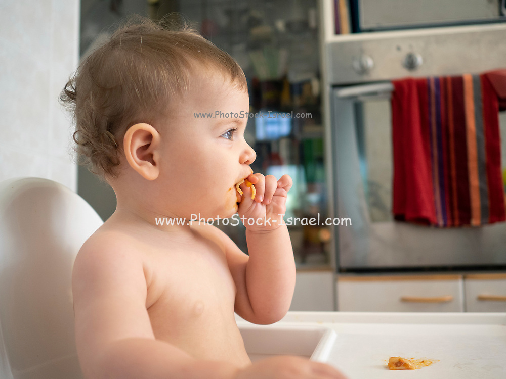 1 year old female baby sits in a high chair waiting for her meal