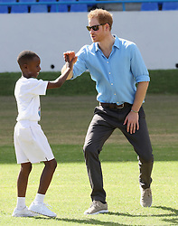Prince Harry high fives a young cricket player as he attends a youth sports festival at the Sir Vivian Richards Stadium in North Sound, Antigua, on the second day of his tour of the Caribbean.