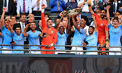Manchester City's Vincent Kompany and Fernandinho lift the Community Shield trophy after the Community Shield match at Wembley Stadium, London.