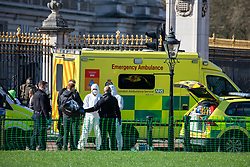 © Licensed to London News Pictures. 16/03/2020. London, UK. Police in masks and medics in protective suits outside Buckingham Palace surround a man (with shoulder bag). It is not clear if he is being arrested. Government ministers warn that the over 70s could face self-isolation for weeks as the Coronavirus disease pandemic continues . Photo credit: Alex Lentati/LNP