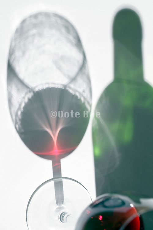 shadow of a wineglass with red wine and a half full bottle