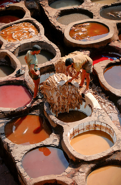 Men working in the dying pits of the tanneries in Fez, Morocco. Leather skins are dyed in the pits for weeks before being made into leather goods.