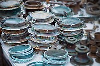 Weathered copper portholes stacked on a table