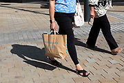 A woman carries a shopping bag from popular British high street fashion retailer Primark on 2nd September, 2021 in Leeds, United Kingdom. Despite a rise in footfall across the UKs high streets, new data has shown more than 8,700 chain stores have closed permanently, with the Covid-19 pandemic seeing consumer habits shifting in favour of shopping online or locally.