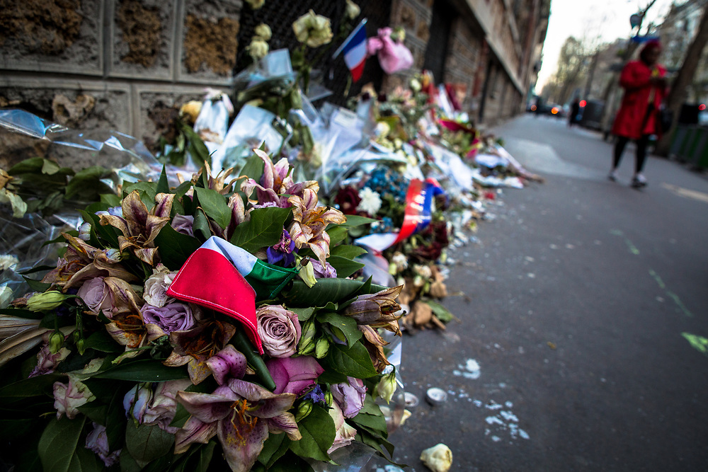 Official memorial plate and a makeshift  flower memorial across the street from the Belle Equipe bar commemorate the terrorist attacks by the Islamic State commited which claimed more than a 100 lives on November 13, 2015.  December 12, 2016.  Paris, France.