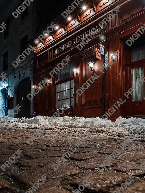 Montreal, Quebec, Canada - January 3, 2021 Facade of Auberge-Restaurant Les Filles du roy in winter viewed from a low angle from the cobbled street in Bonsecours street in Old Port of Montreal