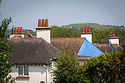 A male roofer sits on a house roof top during a break on the 21st of July 2021 in Folkestone, Kent, United Kingdom. Roofing is one of the most dangerous professions, some roofers in the UK still work without the correct safety equipment.